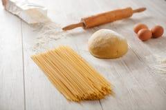 Making fresh spaghetti. Kitchen table with flour and dough spaghetti Stock Photography