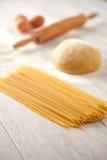 Making fresh spaghetti. Kitchen table with flour and dough spaghetti Stock Photos
