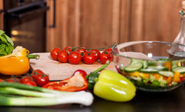 Making a fresh vegetables salad - adding the tomatos Royalty Free Stock Images