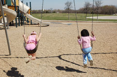 Making friends. Two little girls swing together and make friends at the park. First time for them to meet and play Stock Photo
