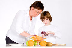 Making the fruit salad. Mother and son making a healthy fruit salad Royalty Free Stock Images