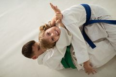 Girl making funny face having aikido battle with friend stock photography
