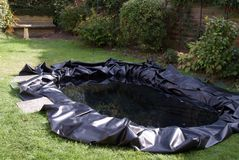 Making a Garden Pond. This image shows the untrimmed butyl rubber liner placed in the hole prepared (see image 15914103) and filled with water Stock Images