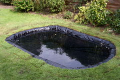 Making a Garden Pond. This image shows the trimmed butyl rubber liner placed in the hole prepared (see image 15914103), filled with water, with grass turf Stock Images