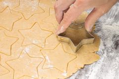 Making ginger bread christmas cookies with metal cutter. Ginger dough and flour Stock Photography