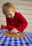 Making gingerbread cookies. Little girl (3 years) cutting out gingerbread cookies for christmas Stock Photo