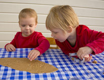 Making gingerbread cookies. Small children (2 and 3 years old) cutting out gingerbread cookies for christmas Royalty Free Stock Photography