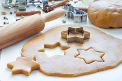 Making gingerbread cookies. Dough, metal cutter and rolling pen on wooden table, spices on background Royalty Free Stock Images