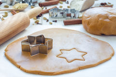 Making gingerbread cookies. Dough, metal cutter and rolling pen on wooden table, spices on background Stock Photo