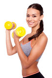 Making good progress. Portrait of a smiling young woman lifting weights against white isolated background Stock Photography