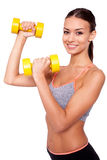 Making good progress. Portrait of a smiling young woman lifting weights against white isolated background Stock Photo