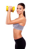 Making good progress. Portrait of a smiling young woman lifting weights against white isolated background Royalty Free Stock Image