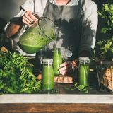 Woman pouring green smoothie from blender to bottle, square crop stock images