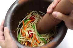Making of green papaya salad. Som tam, thai food, ingredients are mixing and pounding in a mortar Royalty Free Stock Images