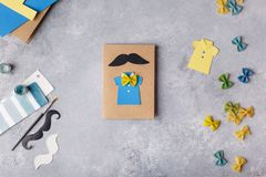 Making greeting card for Fathers Day. Shirt with butterfly from pasta. Card from paper. moustache. Childrens art project. royalty free stock photo