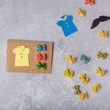 Making greeting card for Fathers Day. Shirt with butterfly from pasta. Card from paper. moustache. Childrens art project. royalty free stock photography