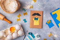 Making greeting card for Fathers Day. Shirt with butterfly from pasta. Card from paper. moustache. Childrens art project. royalty free stock image