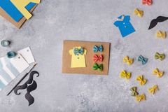 Making greeting card for Fathers Day. Shirt with butterfly from pasta. Card from paper. moustache. Childrens art project. stock image