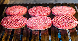 Making and grilling hamburger beef patties on coal grill. Royalty Free Stock Photo