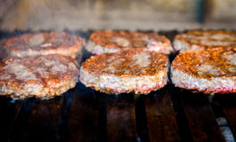 Making and grilling hamburger beef patties on coal grill. Preparing roasted food on barbecue BBQ grill in outdoor fireplace and u-shape fire grid Royalty Free Stock Photo