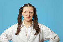 Making a grimace. Fun girl making a grimace on blue background Stock Photos