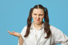 Making a grimace. Fun girl making a grimace on blue background Stock Photo