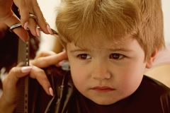 Making the haircut experience enjoyable. Little child given haircut. Small child in hairdressing salon. Little boy with. Blond hair at hairdresser. Cute boys stock image