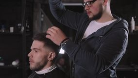 Making haircut look perfect. Young bearded man getting haircut by hairdresser while sitting in chair at barbershop stock video footage