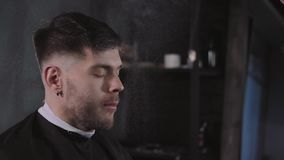 Making haircut look perfect. Young bearded man getting haircut by hairdresser while sitting in chair at barbershop stock video