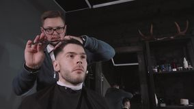 Making haircut look perfect. Young bearded man getting haircut by hairdresser while sitting in chair at barbershop stock footage