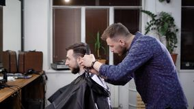 Making haircut. Young bearded man getting haircut by barber while sitting in chair at barbershop stock footage