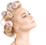 Making hairdo. Closeup portrait of beautiful blond woman with curlers on hair isolated on white background, making hairdo, luxury beauty salon Royalty Free Stock Photos