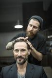 Making hairstyle in barbershop Royalty Free Stock Image