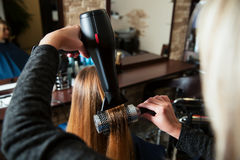 Making hairstyle using hair dryer. Professional women hairdresser making hairstyle using hair dryer for young female in beauty salon royalty free stock photo