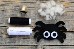 Making a Halloween felt spider decoration. Step. Cute spider ornament for Halloween decor. Craft set on a wooden table Stock Photo