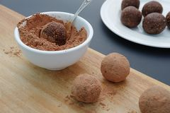 Making handmade chocolate truffles on wooden background. With cacao powder stock image