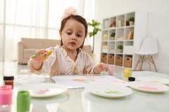 Making handprints. Portrait of pretty little girl making colorful handprints stock photos