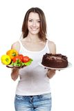 Making hard choice between vegetables and cake Royalty Free Stock Photography