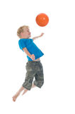 Making A Header. Young boy going to make a header. Will he score? Isolated on a white background. Little movement in arms and legs Royalty Free Stock Photo