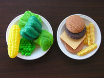 Making healthy food choices. Two plates with plastic play food, one with vegetables the other with hamburger and fries Royalty Free Stock Image