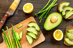 Making healthy lunch with bread, lemon, avocado and knife kitchen top view Royalty Free Stock Image