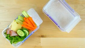 Making healthy salad school lunch boxes, time lapse.