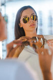 Making her final choice. Beautiful young woman choosing sunglasses to buy while standing in front of the mirror in the optic store Stock Images