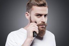 Making his beard perfect. Royalty Free Stock Image