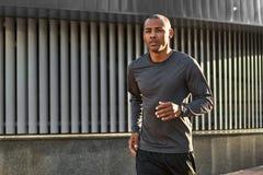 Making his body strong Retrato del primer del hombre africano joven en la ropa de deportes que corre por la mañana contra moderno fotos de archivo libres de regalías