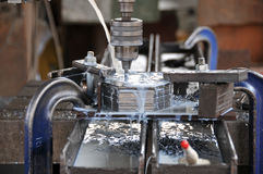 Making hole on metal plates. Making hole on a bunch of hard metal plate with heavy duty drilling machine and applying water to cool it Royalty Free Stock Photos