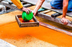 Making Holy Week carpet, Antigua, Guatemala. Making Holy Week carpet using wooden stencils and dyed sawdust in path of religious procession in Spanish colonial stock image