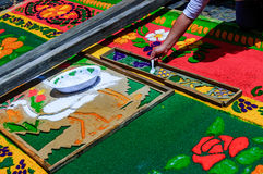 Making Holy Week carpet of sawdust, Antigua, Guatemala. Antigua, Guatemala - April 2, 2015: Local woman makes Holy Week carpet (alfombra) using wooden stencils stock images