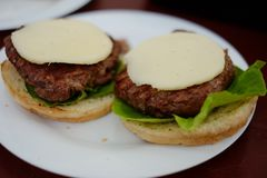 Making homemade burgers. Making burgers: putting some cheese on the burgers stock photo