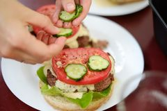 Making homemade burgers. Putting some fresh peaces of cucumbers on the burger during making a burger stock photos